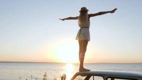 El viaje feliz de la emoción, muchacha aumenta los brazos para arriba en el auto del tejado al aire libre almacen de video