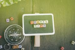 El VIAJE INCLINA el bloque de palabra en señalización y el compás sobre fondo de madera con efecto luminoso Fotos de archivo libres de regalías