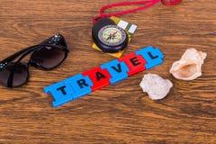 El viaje, las cáscaras, los vidrios y el compás de la inscripción en fondo de madera Foto de archivo libre de regalías