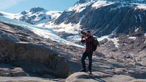 El viajero barbudo con una mochila toma las im?genes del glaciar en Noruega almacen de video