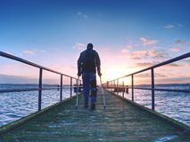 El viajero con la pierna del daño en vendajes permanece en el puente del mar Turista con la pierna quebrada o foto de archivo