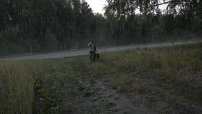 El viajero con una maleta camina a lo largo del borde de la carretera almacen de metraje de vídeo