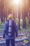 El viajero con una mochila y una espuma se coloca en el bosque Foto de archivo