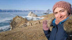 El viajero de la muchacha hace un selfie y agitar su mano en guantes en la cámara Viajero sonriente en el fondo del lago del invi fotos de archivo libres de regalías