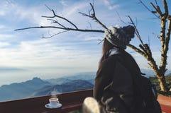 El viajero de la mujer bebe el café en restaurante con vistas al paisaje de la montaña Una mujer turística joven bebe una bebida  imagenes de archivo