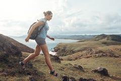 El viajero de la mujer con la mochila va abajo de la montaña en fondo Foto de archivo libre de regalías