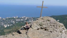 El viajero de la mujer medita en las montañas, sentándose encima de un acantilado en la posición de loto almacen de metraje de vídeo