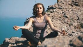 El viajero de la mujer medita en las montañas, sentándose encima de un acantilado en la posición de loto almacen de video