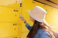El viajero de la mujer que utiliza el servicio del armario y va las vacaciones en la ciudad imagenes de archivo