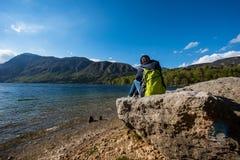 El viajero de la mujer se está sentando en la roca cerca de costa Imagenes de archivo
