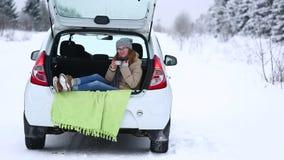 El viajero de la mujer se está sentando en el tronco de un coche almacen de metraje de vídeo