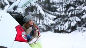 El viajero de la mujer se está sentando en el tronco de un coche y de un té caliente de consumición almacen de metraje de vídeo