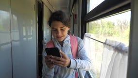 El viajero del adolescente de la muchacha con la mochila hace una pausa la ventana del coche de tren con un smartphone Transporte metrajes