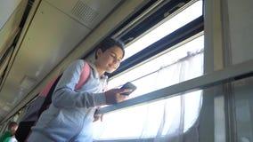 El viajero del adolescente de la muchacha con la mochila hace una pausa la ventana de la forma de vida el coche de tren con un sm metrajes