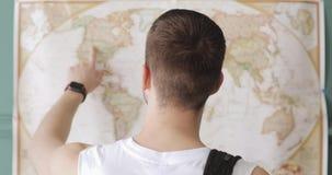 El viajero del hombre está mirando el mapa y está señalando lugares para visitar, detrás visión concepto del recorrido almacen de metraje de vídeo