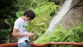 El viajero del hombre que lleva las gafas de sol con el teléfono móvil cerca de una cascada en bosque utiliza smartphone 1920x108 almacen de video
