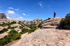 El viajero está permaneciendo entre las rocas de Montserrat cerca de la abadía de Montserrat, Cataluña, España Foto de archivo