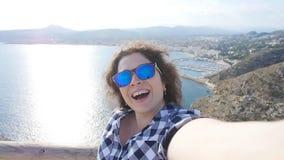 El viajero feliz de la mujer en gafas de sol hace el selfie con el mar y el Mountain View almacen de video
