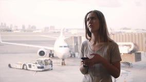 El viajero femenino caucásico joven utiliza smartphone, consigue frustrado después de escuchar el aviso cerca de ventana del aero almacen de metraje de vídeo