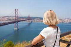 El viajero femenino disfruta de vistas panorámicas de Lisboa y del puente del 25 de abril Foto de archivo