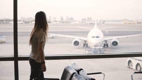 El viajero femenino irreconocible con el bolso camina para arriba a la ventana terminal del salón del aeropuerto para disfrutar d metrajes