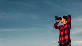 El viajero hermoso de la chica joven mira a través de los prismáticos contra un cielo azul con el espacio de la copia El concepto imagen de archivo libre de regalías