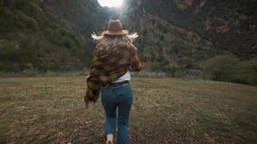 El viajero hermoso de la mujer joven corre libremente a través del campo en naturaleza entre las montañas Lanza un sombrero en el almacen de metraje de vídeo