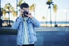 El viajero joven del blogger del inconformista en una chaqueta del dril de algodón transporta la atmósfera de la costa costa con  Imagen de archivo libre de regalías