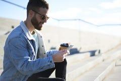 El viajero joven del blogger del inconformista en una chaqueta del dril de algodón vía smartphone conectó con el café de consumic Fotos de archivo libres de regalías