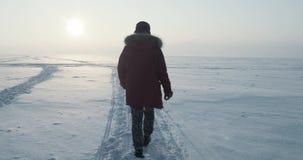 El viajero joven pasa a través de una ventisca en la puesta del sol hermosa Expedición polar almacen de video