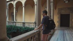 El viajero masculino está examinando la yarda y balcones internos del palacio europeo antiguo almacen de video