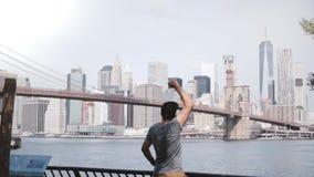 El viajero masculino feliz corre hasta el horizonte famoso épico de la cerca de la orilla del río del puente de Brooklyn de New Y almacen de video