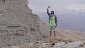 El viajero que toma el selfie con los mouintains hermosos ajardina en el fondo metrajes