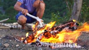 El viajero revuelve el fuego con un palillo almacen de metraje de vídeo