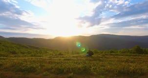 El viajero saluda salida del sol de detrás las montañas contra el cielo azul sin fin metrajes