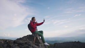 El viajero toma un selfie en las montañas turista femenino joven que se sienta al borde de un acantilado y que toma imágenes ence metrajes