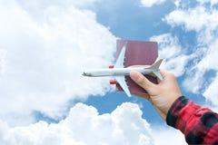 El viajero turístico del aeroplano que se sostiene y del viaje del vuelo del pasaporte vuela en el cielo azul para el aire de la  Imagen de archivo