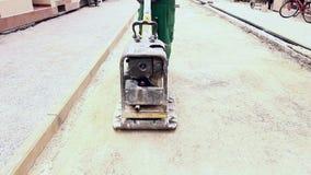 El vibrador está condensando el suelo en el emplazamiento de la obra almacen de metraje de vídeo