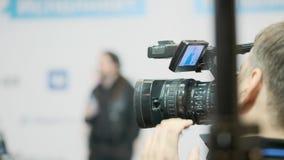 El videocámera mantiene el expediente del funcionamiento del conferenciante pasillo de la presentación metrajes