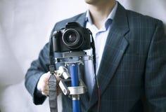 El videographer profesional guarda el steadicam con la cámara en el fondo blanco imagenes de archivo