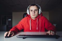 El videojugador adolescente joven juega al partido en casa en su ordenador El hombre joven con el miedo de mirar su monitor de co Fotografía de archivo libre de regalías