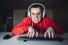 El videojugador emocional juega al juego en el ordenador personal El hombre joven enojado y tiene sus fingeres en el teclado Fotos de archivo libres de regalías