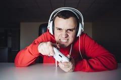 El videojugador emocional juega a los partidos en casa en la palanca de mando El hombre joven juega a los juegos de ordenador usa imagen de archivo libre de regalías