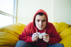 El videojugador joven enfocado juega una palanca de mando del videojuego El hombre joven que juega en la consola Mirada en la cám Imágenes de archivo libres de regalías