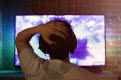 El videojugador o la flámula en auriculares con el micrófono se sienta en casa en sitio oscuro y juegos con los amigos en redes e imagenes de archivo