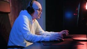 El videojugador profesional juega al videojuego intenso en un ordenador de la PC Hombre joven que juega al juego competitivo en l almacen de video