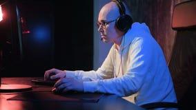 El videojugador profesional juega al videojuego intenso en un ordenador de la PC Hombre joven que juega al juego competitivo en l almacen de metraje de vídeo