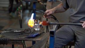 El vidriero utiliza la antorcha para ayudar a moldear el vidrio final 4K metrajes