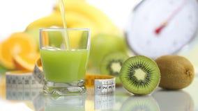 El vidrio adentro vertido jugo del kiwi, escalas del metro de la fruta adieta la comida