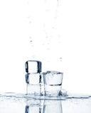 El vidrio con el líquido transparente con los cubos de hielo, salpica y cae Fotografía de archivo